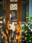 "05 NOVEMBER 2015 - YANGON, MYANMAR: A woman peers out the front door to the home of Aung San Suu Kyi. She lived in house arrest here for more than 15 years. Suu Kyi is now contesting a national election in Myanmar and hosted a press conference at her home. During the press conference, which lasted 90 minutes, Aung San Suu Kyi, the leader of the National League for Democracy (NLD), said that if the NLD won the election she would serve ""above"" the President. When questioned about the Rohingya crisis in western Myanmar, a reporter called the situation ""dramatic"" and Suu Kyi replied the entire country is in a ""dramatic situation"" and the problems of the Rohingya should not be ""exaggerated."" She said the ""great majority of our people remain as poor as ever."" She also said the NLD would make a ""fuss"" if election results were ""suspicious."" Citizens of Myanmar go to the polls Sunday November 8 in what is widely viewed as the most democratic and contested election in Myanmar's history. The NLD is widely expected to win the election.   PHOTO BY JACK KURTZ"