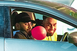 "© Licensed to London News Pictures . 22/12/2018 . Manchester , UK . A man with a balloon in his mouth drives along Peter Street with three passengers . Revellers out in Manchester City Centre overnight during "" Mad Friday "" , named for historically being one of the busiest nights of the year for the emergency services in the UK . Photo credit : Joel Goodman/LNP"