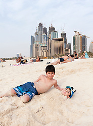 Boys playing in sand at Jumeirah Beach resort district with high rise buildings to rear in Dubai, United Arab Emirates,UAE
