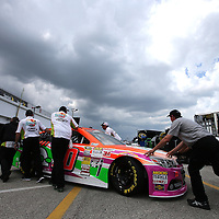 Crew members push the car of Danica Patrick back into her garage area during the first practice session of the 56th Annual NASCAR Coke Zero 400 race at Daytona International Speedway on Thursday, July 3, 2014 in Daytona Beach, Florida.  (AP Photo/Alex Menendez)