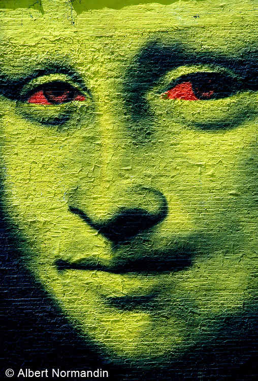 Mona Lisa face with red eyes painted on brick wall, Broome Street