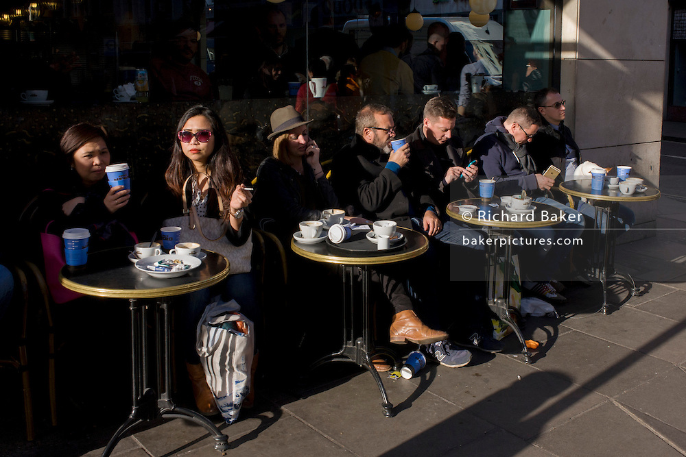 Afternoon coffee drinkers sit outside Caffe Nero in Old Brompton Street in Soho.