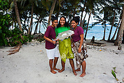 Young samoan girls holding their fresh catch, Ofu Island, Manu´a island group, American Samoa, South Pacific
