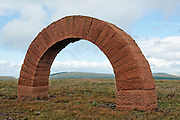 Andy Goldworthy's red sandstone Striding Arches land art sculpture on the summit of Benbrack near Cairnhead, Southern Uplands, Scotland. Distant arch on Colt Hill visible in the distance