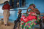 Lusseini and Lacine, both 4 and suffering from malaria and diarrhea, wait with their grandmother Matila, 60, while their mother Katy Cherif, 40, gets prescription drugs for them at the pharmacy counter of the Libreville health center in Man, Cote d'Ivoire on Wednesday July 24, 2013.