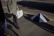 A discarded broken umbrella and a person walking past with a brolley shop bag in Charing Cross Road, central London.