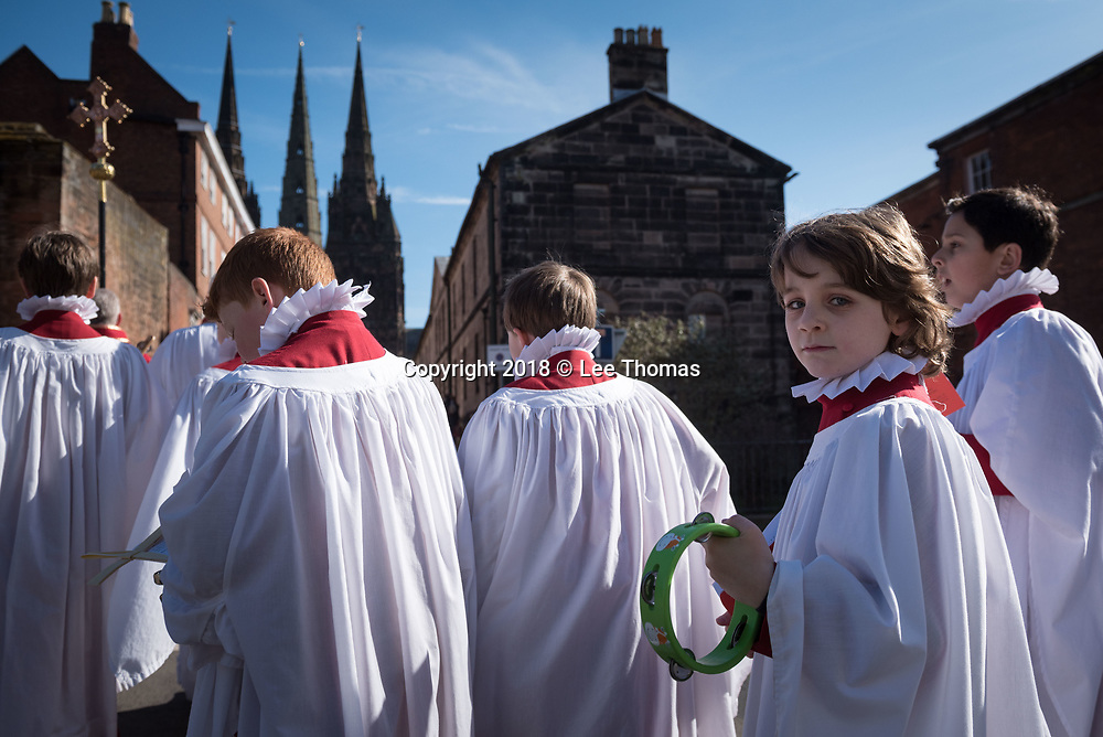 "Lichfield, Staffordshire, UK. 25th March 2018.  A fine spring morning greeted worshipers, members of the clergy and a donkey for the annual Palm Sunday procession through the medieval streets of Lichfield. The ""Triumphal Entry"" procession (when Jesus entered Jerusalem cheered on by a crowd, riding on a donkey) began at Speakers' Corner in the Staffordshire city and ended at the west door of the famous Cathedral. Pictured: Choristers take part in the procession with the famous three spires of Lichfield Cathedral in the background. // Lee Thomas, Tel. 07784142973. Email: leepthomas@gmail.com  www.leept.co.uk (0000635435)"
