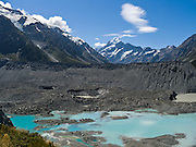 Seen from Kea Point Track, the peak of Aoraki / Mount Cook rises to 3755 meters or 12,349 feet in Aoraki / Mount Cook National Park, South Island, New Zealand. The moraine of Mueller Glacier makes a large pile of gravel which dams the powder blue terminal lake. Start the Kea Point Track from Mt Cook Village or from a shortcut at the end of Hooker Valley Road. In 1990, UNESCO honored Te Wahipounamu - South West New Zealand as a World Heritage Area.