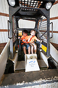 Buckled in for safety, Holden Miller, 5, and his cousin, Willem Fuller, 4, pretend to drive a Bobcat digger during the fourth annual International Student Farm Outing at the Schultz Family Farm in Cottage Grove, Wis., on June 24, 2012. Co-sponsored by the Schultz family and the University of Wisconsin-Madison International Student Services (ISS), the event introduced more than 100 UW-Madison international students and their families, and friends of the Schultz family to agricultural life in rural Wisconsin.