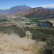 A competitor falls during the NZBNZ South Island Downhill Cup mountain bike downhill series held on The Remarkables face with a stunning backdrop of the Wakatipu Basin. 150 riders took part in the two day event.  Queenstown, Otago, New Zealand. 9th January 2012. Photo Tim Clayton