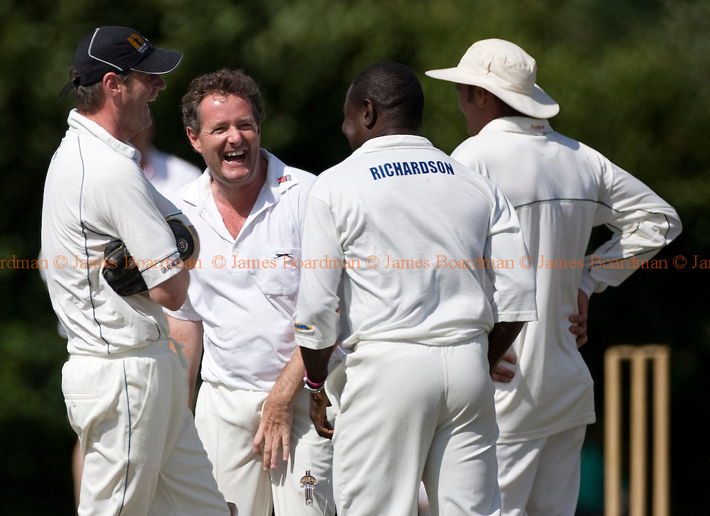 JAMES BOARDMAN / 07967642437.Piers Morgan and Richie Richardson celebrate a wicket during Piers Morgan's XI match against Newick Cricket Club in East Sussex. West Indian Legends Richie Richardson and Curtly Ambrose both played for Piers Morgan's side, whilest American TV personality Jerry Springer watched from the pavilion.