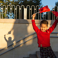 China, Beijing, Young boy waves Chinese flags while walking up subway stairs at sunset on autumn evening