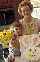 Grandmother and grandson display traditional Easter Bunny cake and bread.