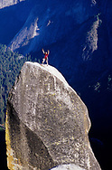 YOSEMITE, CA - A rock climber stands on the summit of the Lost Arrow Spire in Yosemite, CA.  The Lost Arrow Spire sits next to Yosemite Falls and was first climbed in 1947 by John Salathe.  (releasecode: jk_mr1008) (Model Released)
