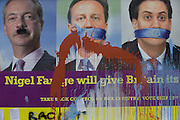 Splashed paint over the anti-EU membership 'UK Independence Party's (UKIP) political billboard that shows leader Nigel Farage (with daubed Hitler moustache) and a gagged Prime Minister David Cameron and Labour party leader Ed Milliband - all silent against a bullying European Union, seen in East Dulwich, south London. The ad is displayed before European elections on 22nd May.