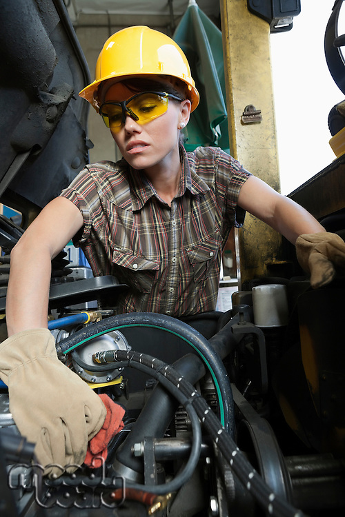 Female industrial worker cleaning vehicle part