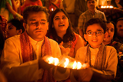 People worshipping by candlelight in celebration of Navratri; the Hindu festival of Nine Nights,