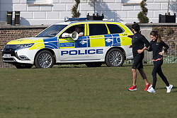 © Licensed to London News Pictures. 27/03/2020. London, UK. Police use a megaphone in Greenwich Park to instruct members of the public who aren't using the park to exercise to move on. The Government has announced a lockdown to slow the spread of Coronavirus and reduce pressure on the NHS. Photo credit: George Cracknell Wright/LNP