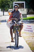 "20 JUNE 2009 - PHOENIX, AZ: Melvin Holmes, from Phoenix, rides his bike home after picking up fresh produce at the ""Farmers' Market"" at the Cultural Cup. The Farmers' Market is one of the food bank outreach programs of the Cultural Cup. One Saturday a month, they distribute fresh fruit and vegetables before the walk in clinic opens. Holmes said he visits the food bank at the Cultural Cup every month or so to supplement the food he buys at a grocery store. The walk in clinic at the Cultural Cup Food Bank started two years ago when Cultural Cup founder Zarinah Awad wanted to expand the food bank's outreach and provide basic medical care for the people who use the food bank. The clinic sees, on average, 7 - 11 patients a week. Awad said that as the economy has worsened since the clinic opened and demand has steadily increased. She attributes the growth to people losing their jobs and health insurance. The clinic is staffed by volunteers both in the office and medical staff. Adults are seen every Saturday. Children are seen one Saturday a month, when a pediatrician comes in. Awad, a Moslem, said the food bank and clinic are rooted in the Moslem tradition of Zakat or Alms Giving, the giving of a small percentage of one's income to charity which is one of the Five Pillars of Islam.   PHOTO BY JACK KURTZ"