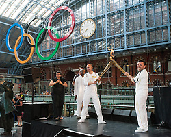 © Licensed to London News Pictures. 26/07/2012. London, UK.  London 2012 Olympics - the Olympic Torch at on its penultimate day (Day 69) of the Olympic Torch Relay at St Pancras International rail station .  Luke Corduner hands the torch over to Danny McCubbin.  Left - Luke, Right - Danny.  Luke lights Danny's torch.  Photo credit : Richard Isaac/LNP