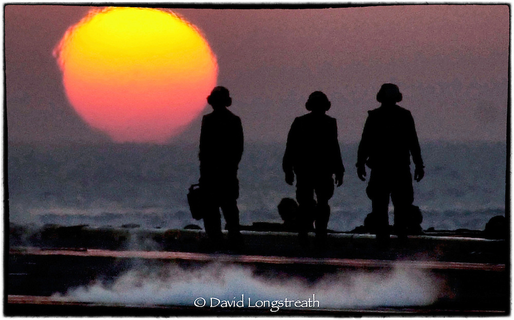 "In this ""Signature Series"" image by David Longstreath, US sailors on the flight deck of the carrier USS Theodore Roosevelt welcome the dawn during flight operations in the Arabian Sea against the Taliban in Afgahistan."