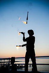 © Licensed to London News Pictures.<br /> Aberystwyth Wales UK,27/02/2019.<br /> A man juggling with fire on the promenade  Aberystwyth as the sun sets, making the most of the sensationally hot and sunny 'winter' weather  while it lasts .  The weather is forecast to start to deteriorate from tomorrow, with more typical windy and cooler conditions expected at the beginning of March<br /> Photo credit Keith Morris / LNP