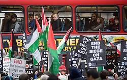 © London News Pictures. 27/12/2011. London, UK.  People on a bus in London watch as they pass by a protest Protestors outside the Israeli Embassy in Kensington, London on December 27th, 2011 to demonstrate on the 3rd anniversary of the beginning of the 3 week Israeli attack on Palestinian people in Gaza in December 2008. Photo credit : Ben Cawthra/LNP