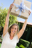 Mid-adult woman holding aloft her birthday present, smiling