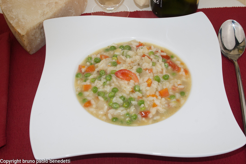 risi e bisi traditional recipe of veneto side view close-up from above on white square dish,italian food