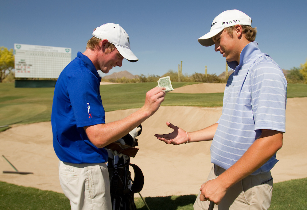 American Junior Golf Association player Grayson Murray, left, pays a buck on a friendly wager to Jordan Spieth at the Thunderbird International Junior tournament.