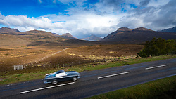 Car and mountains of Assynt on the North Coast 500 scenic driving route in northern Scotland, UK
