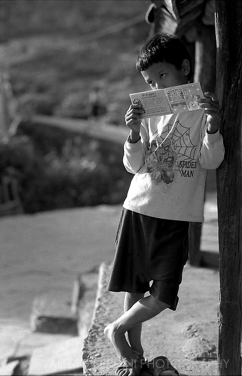 A young boy distracted while he was reading a booklet.