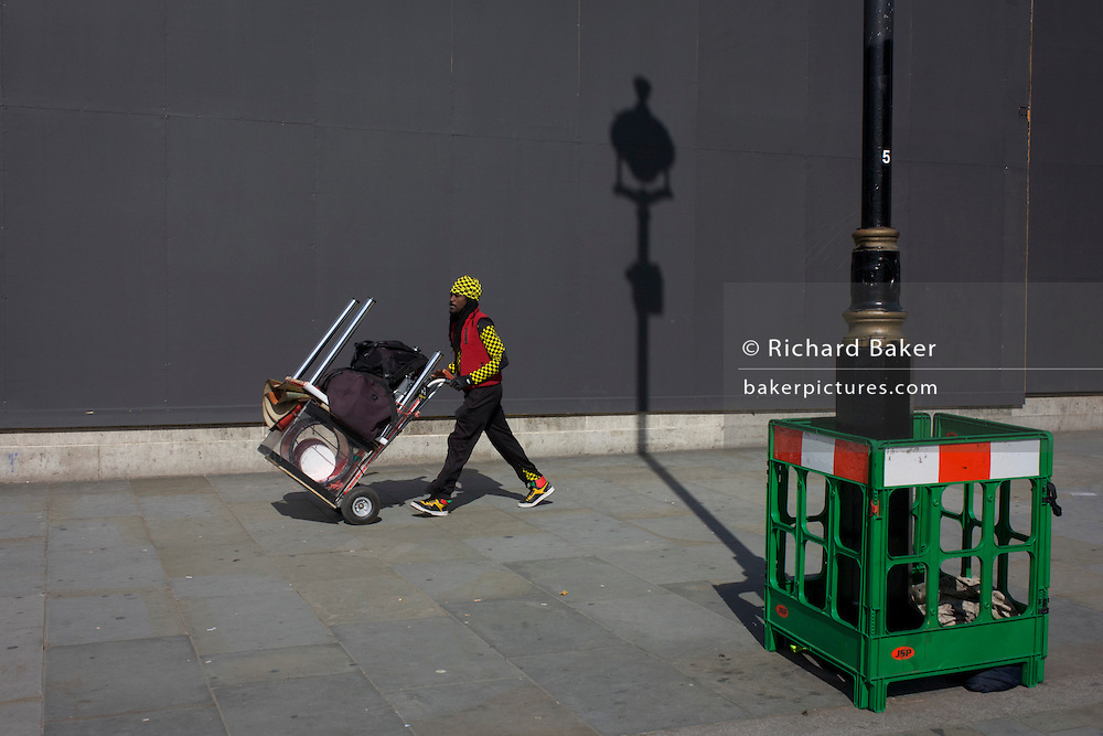Busker walks with equipment with a lamp post shadow against a grey construction hoarding in central London's Trafalgar Square.