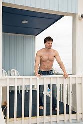 shirtless man standing on an oceanfront balcony