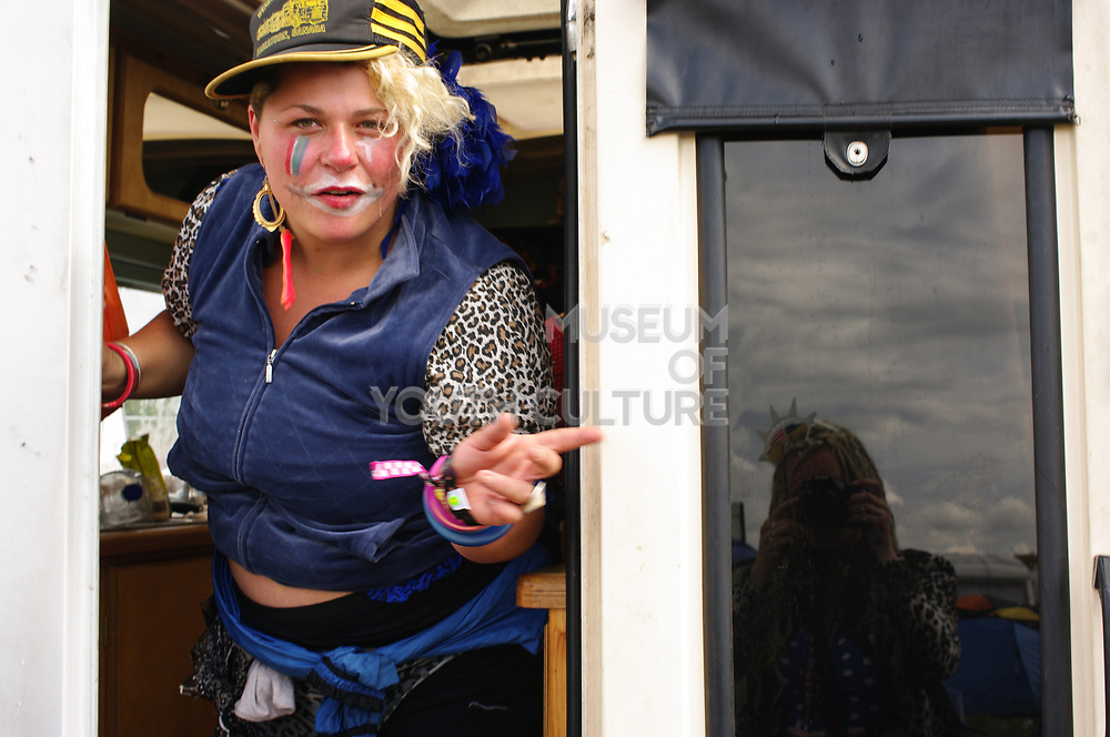 A woman with faceprint emerges from her van, Boomtown, Matterley Estate, Alresford Road, near Winchester, Hampshire, UK, August, 2010