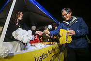 A supporter receives a flower for offering to a memorial statue honoring 'Comfort Women' at Glendale Peace Monument during a candlelight vigil in remembrance and support of 'Comfort Women', Japanese military sexual slavery victims during World War II, on January 5, 2016, in Glendale, California. AFP PHOTO / Ringo Chiu