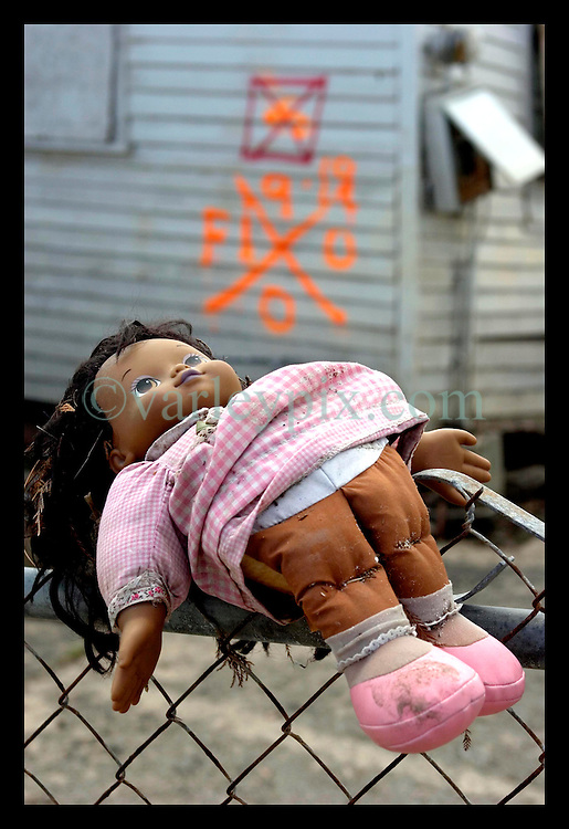 1st Oct, 2005. Hurricane Katrina aftermath, New Orleans, Louisiana. Lower 9th ward. The remnants of the lives of ordinary folks, now covered in mud as the flood waters recede. A child's doll remains snagged to the top of a fence, spray paint in the background shows no bodies were recovered from the house.