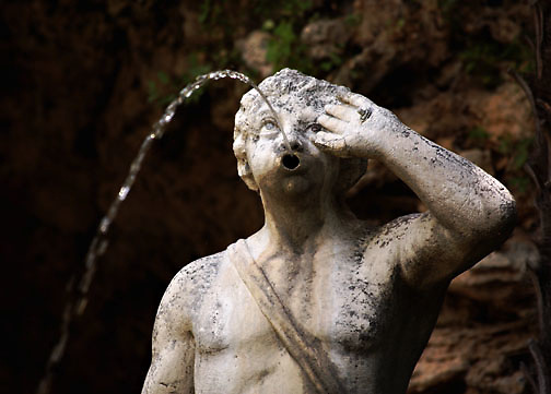Statue of a personage as a fountain, water spouting from his/her open mouth.