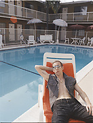 Young man reclining on the side of a swimming pool at a hotel.