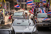 "15 JANUARY 2014 - BANGKOK, THAILAND: An anti-government protestor stands in the sunroof of her Mercedes Benz and waves Thai flags during an anti-government motorcade in Bangkok. Tens of thousands of Thai anti-government protestors continued to block the streets of Bangkok Wednesday to shut down the Thai capitol. The protest, ""Shutdown Bangkok,"" is expected to last at least a week. Shutdown Bangkok is organized by People's Democratic Reform Committee (PRDC). It's a continuation of protests that started in early November. There have been shootings almost every night at different protests sites around Bangkok. The malls in Bangkok are still open but many other businesses are closed and mass transit is swamped with both protestors and people who had to use mass transit because the roads were blocked.    PHOTO BY JACK KURTZ"