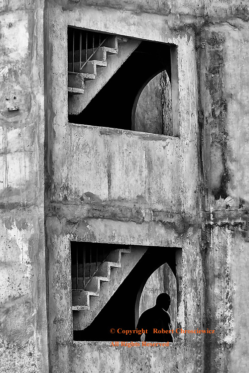 Mirrored Existence (B&W): Windows of a new concrete apartment complex reveal identical industrialised residences, save for a solitary departing silhouette, Trinidad Cuba.