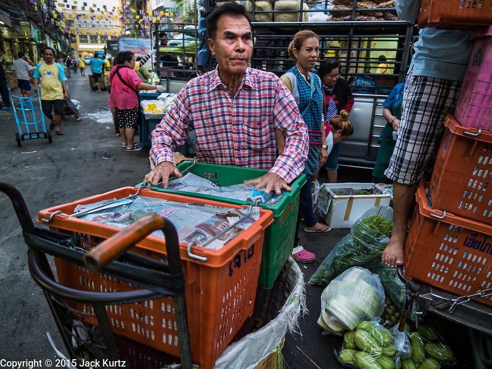 """21 DECEMBER 2015 - BANGKOK, THAILAND:  A man sets up his produce stand in Pak Khlong Talat, also called the Flower Market. The market has been a Bangkok landmark for more than 50 years and is the largest wholesale flower market in Bangkok. A recent renovation resulted in many stalls being closed to make room for chain restaurants to attract tourists. Now Bangkok city officials are threatening to evict sidewalk vendors who line the outside of the market. Evicting the sidewalk vendors is a part of a citywide effort to """"clean up"""" Bangkok.      PHOTO BY JACK KURTZ"""