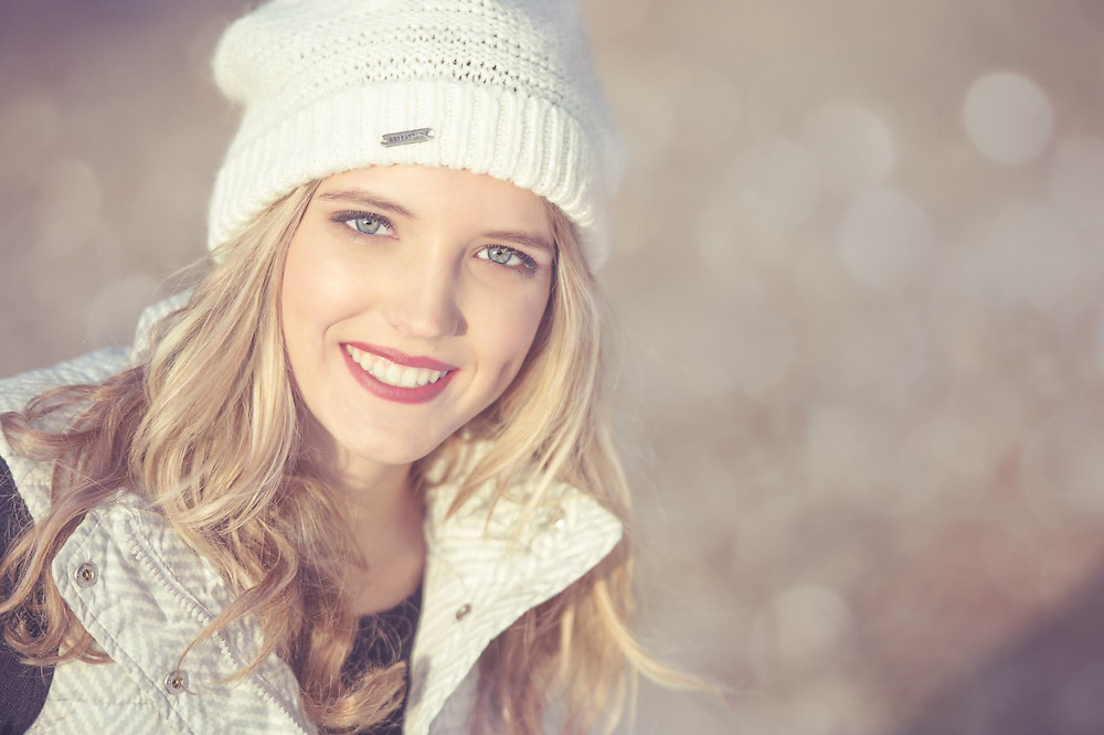 Nashville Senior Picture a closeup of a blonde Senior girl smiling and wearing a white beanie and snow jacket