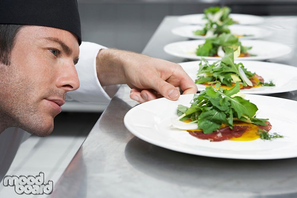 Male chef preparing salad in kitchen close-up