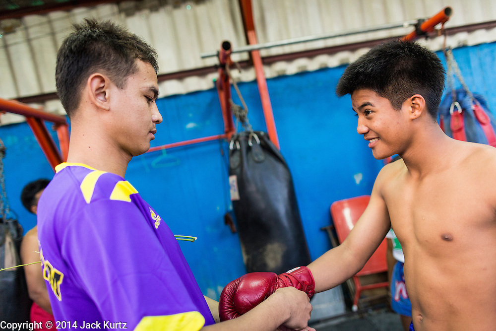 23 DECEMBER 2014 - BANGKOK, THAILAND: Boxers put their gloves on before sparring at the Kanisorn gym in Bangkok. The Kanisorn boxing gym is a small gym along the Wong Wian Yai - Samut Sakhon train tracks. Young people from the nearby communities come to the gym to learn Thai boxing. Muay Thai (Muai Thai) is a mixed martial art developed in Thailand. Muay Thai became widespread internationally in the twentieth century, when Thai boxers defeated other well known boxers. A professional league is governed by the World Muay Thai Council. Muay Thai is frequently seen as a way out of poverty for young Thais. Muay Thai professionals and champions are often celebrities in Thailand.     PHOTO BY JACK KURTZ