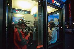 IRELAND DUBLIN MAR00 - Two Dubliners use Eircom Phone boxes. Eircom is a newly formed company, formerly known as Irish Telecom or Telecom Ireann... jre/Photo by Jiri Rezac. . © Jiri Rezac 2000. . Tel:   +44 (0) 7050 110 417. Email: info@jirirezac.com. Web:   www.jirirezac.com
