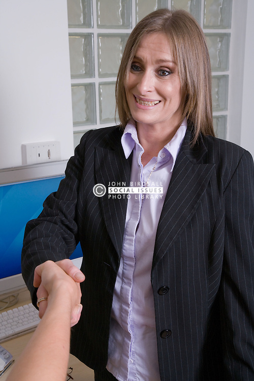 Business woman shaking hands with a person whom they have just secured a successful business deal,