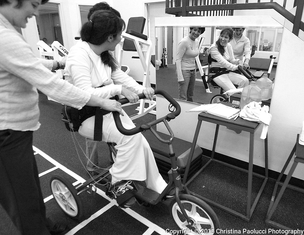 Brooke smiles in the mirror to herself as she passes it by while riding the tricycle at Team Rehab in Decorah, Iowa.  <br /> (Rochester Post-Bulletin, Christina Paolucci)