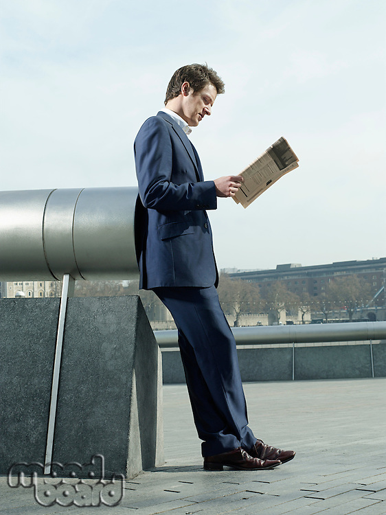 Young man in suit leaning on pipe outdoors reading paper side view