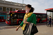A masked Asian lady walks southwards over London Bridge, from the City of London - the capital's financial district founded by the Romans in the 1st century - to Southwark on the south bank, on 3rd September 2018, in London, England.